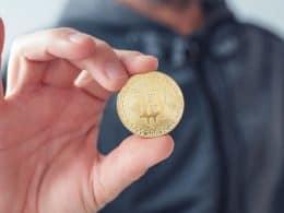 homem segurando moeda